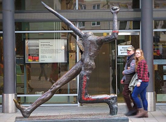 """Wolfgang Mattheuers bronsskulptur """"Jahrhundertschritt"""" (""""Century Step"""") från 1984. En allegori av Tysklands frenetiska historia. Figuren med sitt lilla huvud verkar springa framåt och visar samtidigt den kommunistiska näven och Hitlerhälsningen. Den står utanför Zeitgeschichtlichen Forum Leipzig."""
